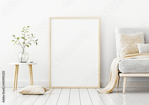 Photo Poster mockup with vertical frame standing on floor in living room interior with sofa, beige pillow and branch in glass vase on empty white wall background