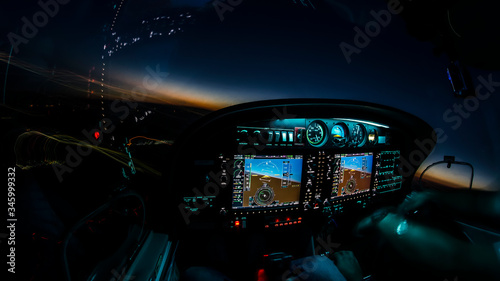 Fotografia Lightened up cockpit and avionics in aircraft flying at night with beautiful twi