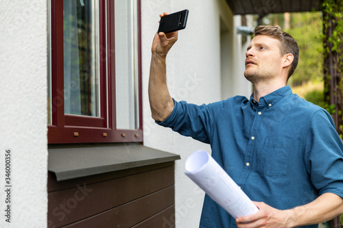real estate appraiser taking pictures of property with phone Wallpaper Mural