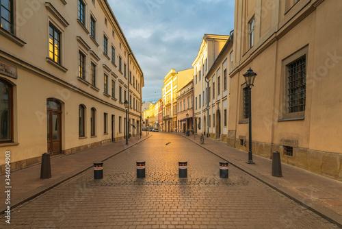Fototapeta Oświetlona słońce zabytkowa ulica w centrum miasta. Z przodu słupki ograniczające wjazd obraz