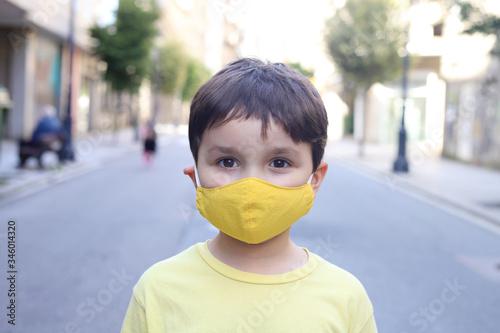 niño en medio de la calle con mascarilla casera de tela debido a la pandemia del Fototapet
