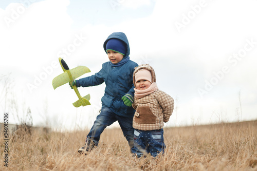 Fototapety, obrazy: Summer holidays - love romance and people concept. Happy children enjoying summer vacation. Little children with toy airplane in a field at sunset