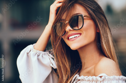 Fotografía Portrait of a beautiful young woman with smile and sunglasses in the city