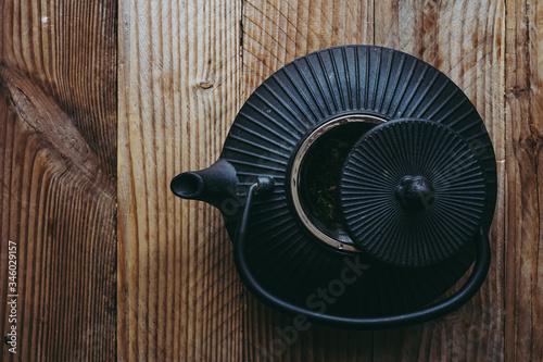 Fototapeta Théière en fonte noire sur un fond en bois obraz na płótnie