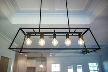 Hanging Retro Black Metal Iron Chandelier Lighting Fixture With Vintage Bulbs Hanging In A Dining Room Of A New Construction House