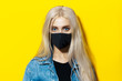 canvas print picture - Studio portrait of young blonde girl wearing black respiratory medical face mask against coronavirus. Background of yellow color.