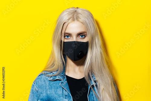Obraz na plátne Studio portrait of young blonde girl wearing black respiratory medical face mask against coronavirus
