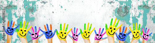 Many brightly painted children's hands with smileys, isolated on white background banner panorama with speckled spotted turquoise paint blobs, with space for text