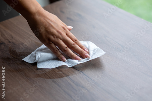 Cuadros en Lienzo Woman cleaning home office table surface with wet wipes stock photo
