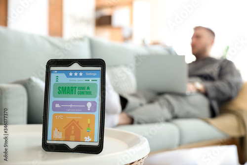 Tablet computer with application of smart home automation on table in room Canvas Print