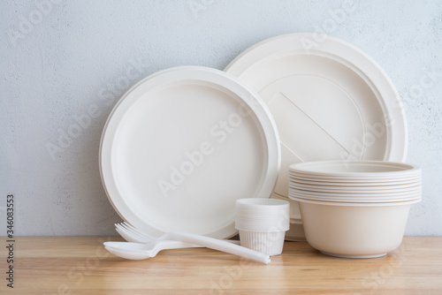 Natural eco-friendly disposable utensils (fork, spoon, dish plate, bowl) made of fiber of bagasse and bamboo on wooden table with white wall background Canvas Print