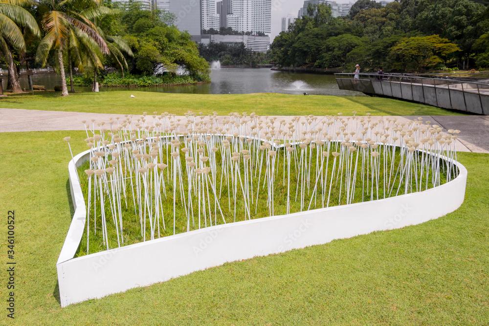 Large white decorative heart with flowers in Perdana Botanical Garden. - obrazy, fototapety, plakaty