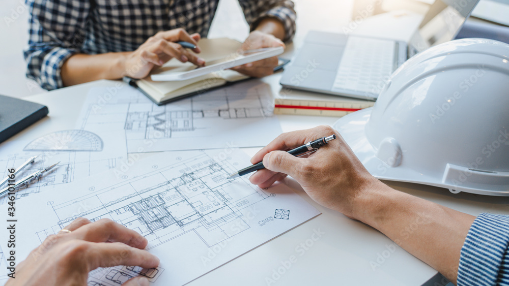 Fototapeta engineer Hand Drawing Plan On Blue Print with architect equipment discussing the floor plans over blueprint architectural plans at table in a modern office.
