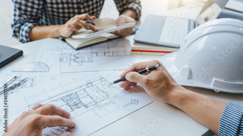 Obraz engineer Hand Drawing Plan On Blue Print with architect equipment discussing the floor plans over blueprint architectural plans at table in a modern office. - fototapety do salonu