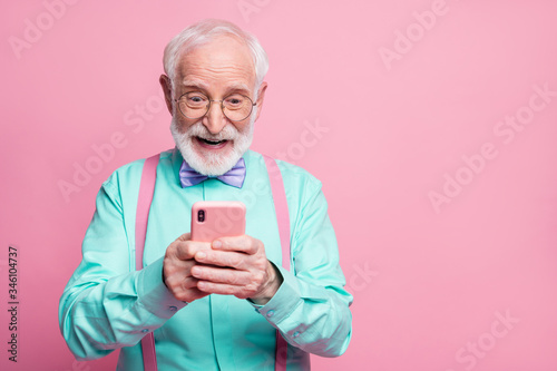 Fototapeta Portrait of surprised crazy shocked old man use smartphone read social media news enjoy comments wear teal outfit purple violet bow tie isolated pastel pink color background obraz