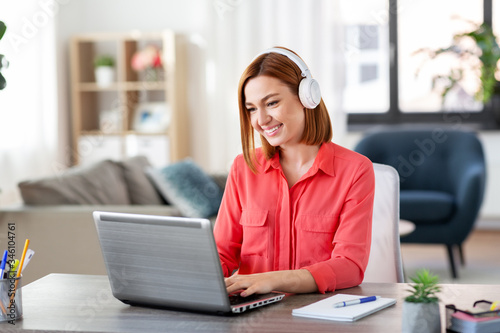 Obraz remote job, technology and people concept - happy smiling young woman in headphones with laptop computer working at home office - fototapety do salonu