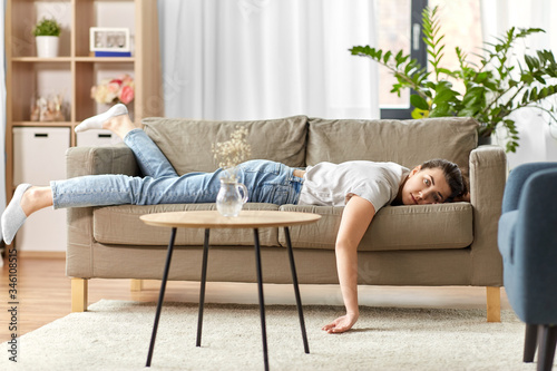 people, boredom and depression concept - bored or lazy young woman lying on sofa Canvas Print