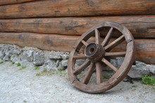 Vintage Wheel From The Cart On The Background Of A Log Wall