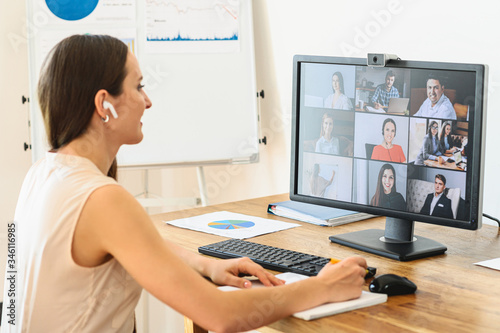 Obraz Video conference with colleagues, coworkers. A young businesswoman using application on pc in office for online conversation with coworkers. - fototapety do salonu