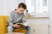 Young Teenage Boy Sitting Reading A Book