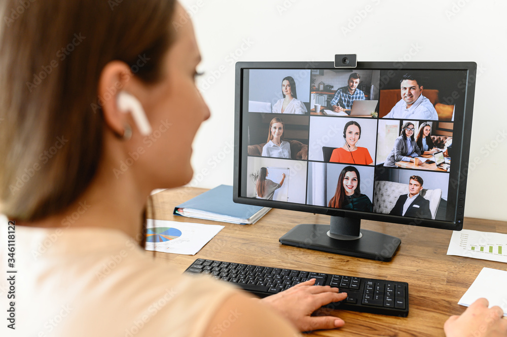 Fototapeta Video call, video meeting. A young woman connect with a many employees together via video, she sits at office space and looks at webcam, rear view