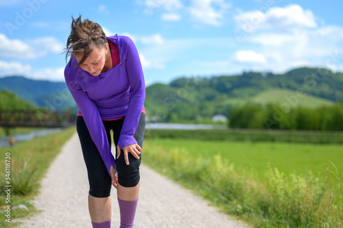 Foto Woman jogger stopping to check an injured knee
