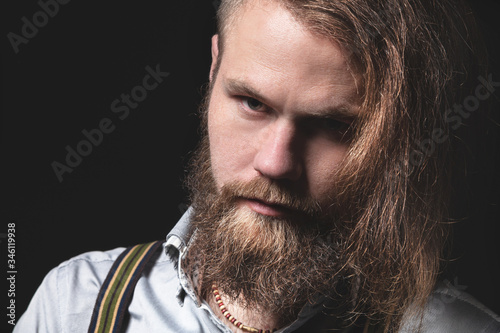 Contrasting low key portrait of a bearded long-haired stylish brutal man in a gray shirt with suspenders sternly looks at the camera Fototapet