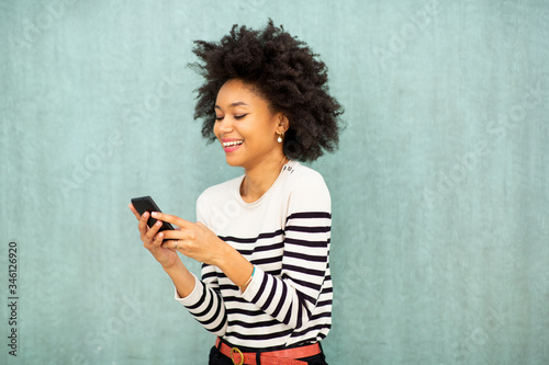 smiling young african american woman looking at phone text message by green background