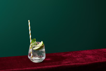High Angle View Of Old Fashioned Glass With Golden Rim With Mojito And Striped Drinking Straw Isolated On Green