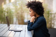canvas print picture - Side of young african american business woman sitting with laptop computer