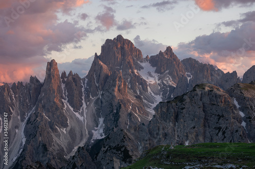 Платно Mountain landscape in the European Dolomite Alps underneath the Three Peaks with alpenglow during sunset, coloured clouds in the sky, South Tyrol Italy