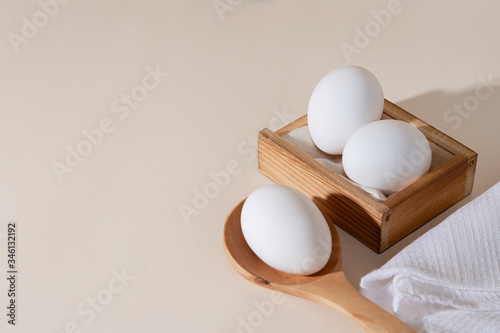 Chicken eggs in a wooden box on beige background with copy space, product with a Canvas Print