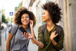 two happy female black friends walking in city with mobile phone listening to music with earphones