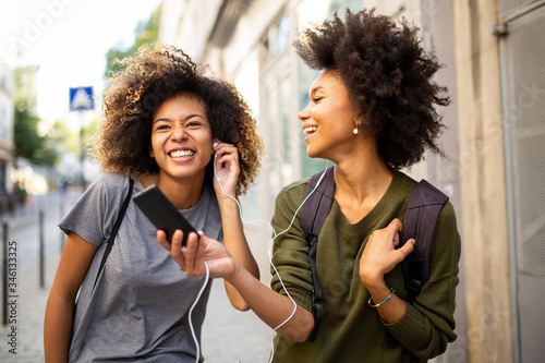Fototapeta two happy female black friends walking in city with mobile phone listening to music with earphones obraz