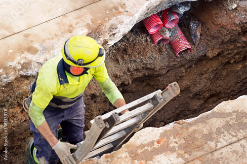 construction worker for restoir and repair pipes for underground electrical wiri Fototapet