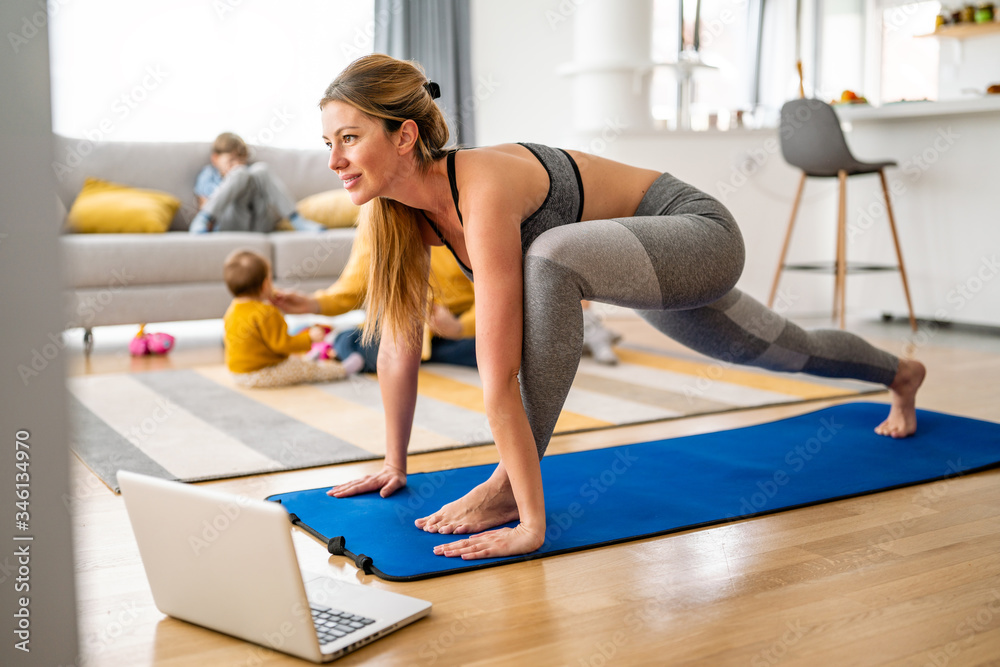 Fototapeta Young woman is exercising yoga at home. Fitness, workout, healthy living and diet concept.