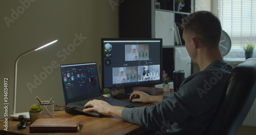Man working on computer with Two Monitors Color Correction Post Production video or photo in Progress Closeup Wallpaper Mural