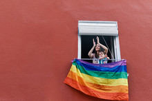Young Woman In A Mask Clapping From The Window With The Gay Flag