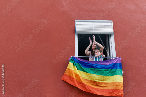 Fototapeta young woman in a mask clapping from the window with the gay flag