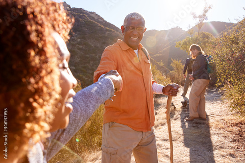 Fototapeta Man Helping Woman On Trail As Group Of Senior Friends Go Hiking In Countryside Together obraz na płótnie