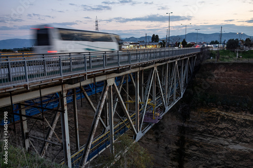 Obraz na plátne Corinth Canal old bridge with a fast driving bus creating a motion blur effect i