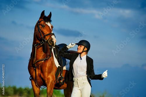 Fototapeta Girl equestrian rider riding a beautiful horse  in the rays of the setting sun. Horse theme obraz