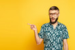 bearded guy in glasses pointing with finger aside on yellow