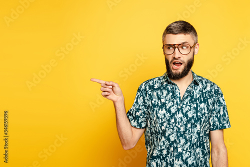 Fotografía bearded guy in glasses pointing with finger aside on yellow