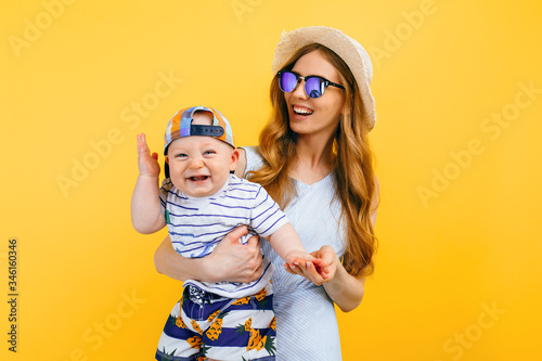 Fotomural Happy beautiful mother in a hat and sunglasses, holds a little child, on an isolated yellow background