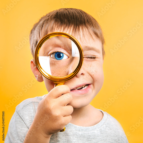 Child see through magnifying glass on the color yellow backgrounds Canvas Print