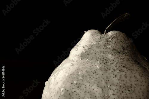 Photo Detail of a fresh, organic Green Anjou pear fruit with water drops against black background