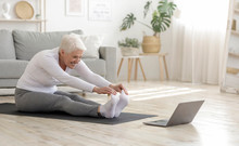 Active Senior Woman Doing Warming Stretching Exercises In Front Of Laptop