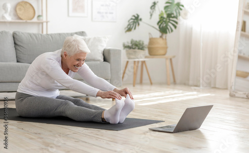 Active Senior Woman Doing Warming Stretching Exercises In Front Of Laptop Wallpaper Mural
