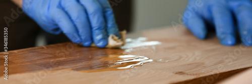 Fotografia Man varnishing table at workshop